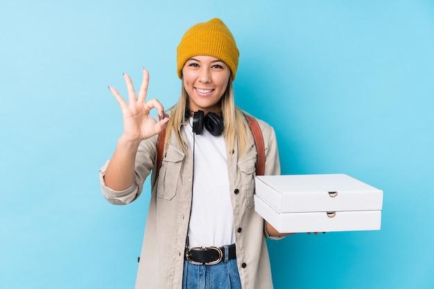 Молодая кавказская женщина, держащая пиццу, изолировала веселую и уверенную демонстрацию жестов.