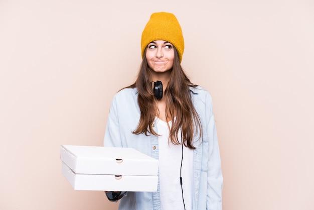 Молодая кавказская женщина, держащая изолированную пиццу, смущена, чувствует себя сомнительной и неуверенной.