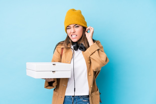 Young caucasian woman holding pizzas isolated covering ears with hands.