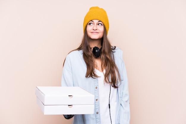Молодая кавказская женщина держит изолированную пиццу, мечтающую о достижении целей и задач