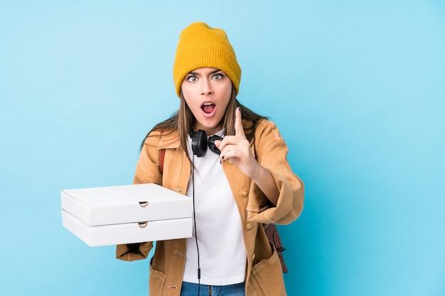 Молодая кавказская женщина держа пиццы изолировала иметь идею, концепцию воодушевленности.