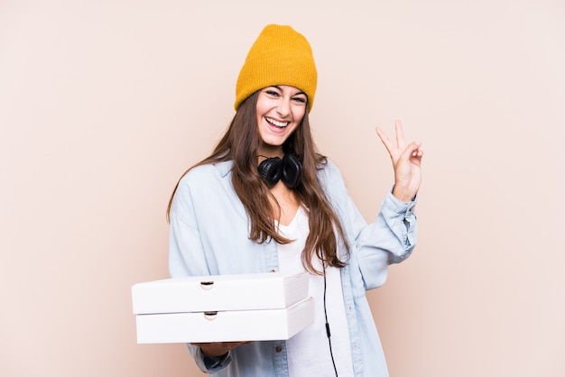 Young caucasian woman holding pizzas isolated joyful and carefree showing a peace symbol with fingers.