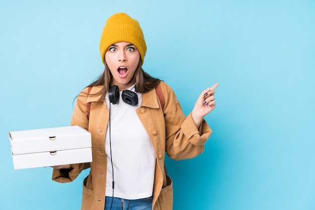 Young caucasian woman holding pizzas isolated pointing to the side