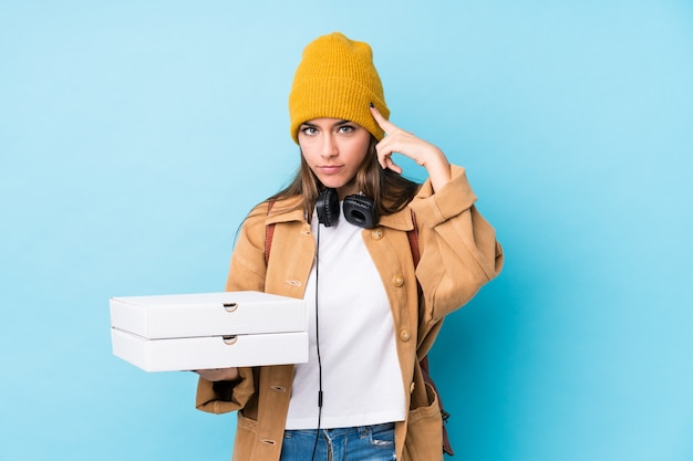 Young caucasian woman holding pizzas isolated pointing temple with finger, thinking, focused on a task.