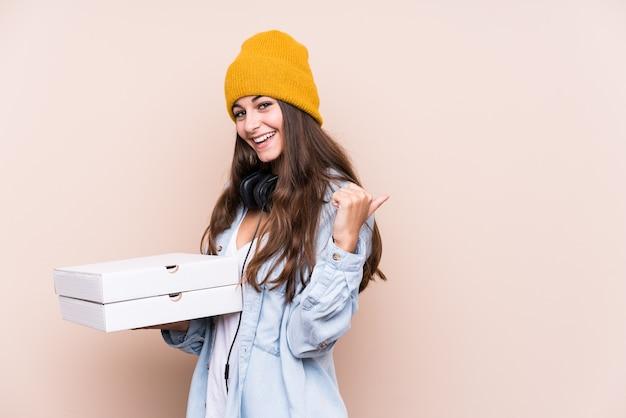 Молодая кавказская женщина, держащая пиццу изолировала точки с большим пальцем, смеясь и беззаботно.