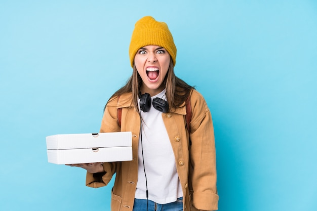 Young caucasian woman holding pizzas isolated screaming very angry and aggressive.