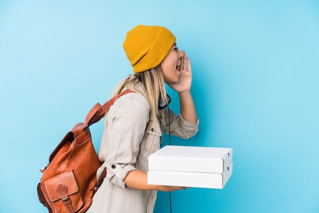 Young caucasian woman holding pizzas isolated shouting and holding palm near opened mouth.
