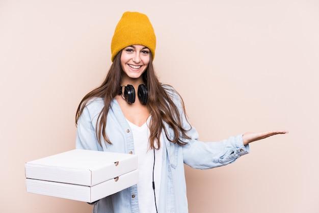 Молодая кавказская женщина, держащая изолированную пиццу, показывает пространство для копии на ладони и держит другую руку на талии.