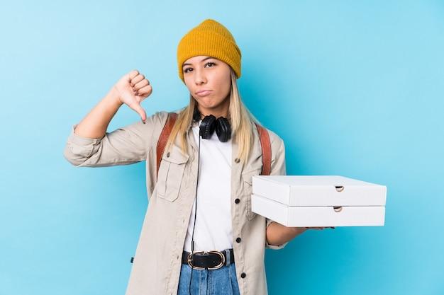 Молодая кавказская женщина держа пиццы изолировала показывать жест нелюбов, большие пальцы руки вниз. концепция несогласия.
