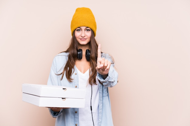 Young caucasian woman holding pizzas isolated showing number one with finger.