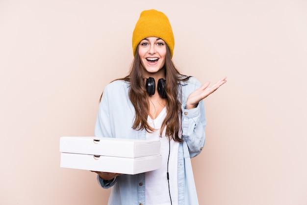 Молодая кавказская женщина, держащая изолированные пиццы, удивлена и шокирована.