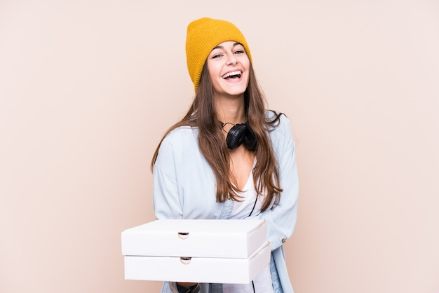 Young caucasian woman holding pizzas laughing and having fun.