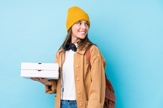 Young caucasian woman holding pizzas looks aside smiling, cheerful and pleasant.