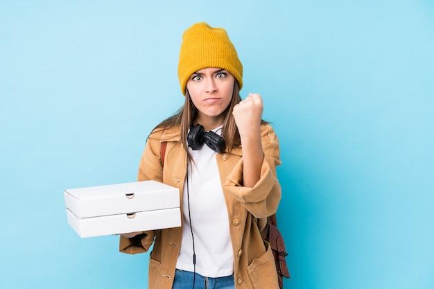 Молодая кавказская женщина держа пиццу показывая кулак