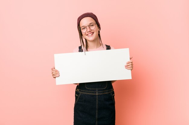 Young caucasian woman holding a placard happy, smiling and cheerful.
