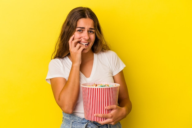 Young caucasian woman holding a popcorns isolated on yellow background  biting fingernails, nervous and very anxious.