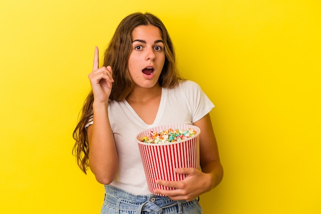 Young caucasian woman holding a popcorns isolated on yellow background  having an idea, inspiration concept.