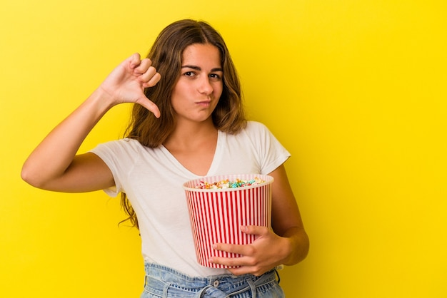 Young caucasian woman holding a popcorns isolated on yellow background  showing a dislike gesture, thumbs down. disagreement concept.