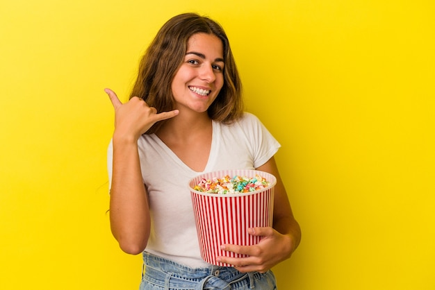 Young caucasian woman holding a popcorns isolated on yellow background  showing a mobile phone call gesture with fingers.
