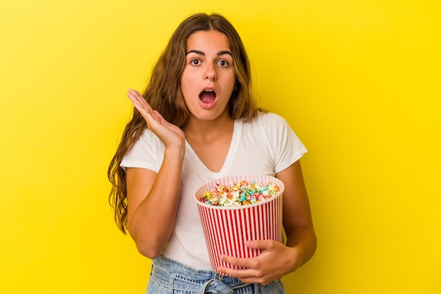 Young caucasian woman holding a popcorns isolated on yellow background  surprised and shocked.