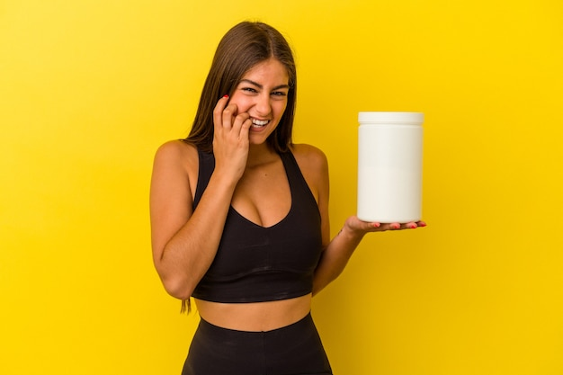 Young caucasian woman holding a protein bottle isolated on yellow background biting fingernails, nervous and very anxious.