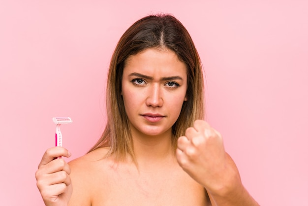Young caucasian woman holding a razor blade isolated young caucasian woman holding a hairbrush isolated , aggressive facial expression.< mixto >