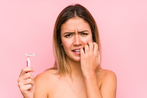 Young caucasian woman holding a razor blade isolated young caucasian woman holding a hairbrush isolated biting fingernails, nervous and very anxious.< mixto >