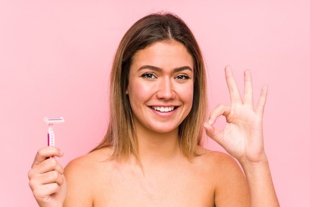 Young caucasian woman holding a razor blade isolated young caucasian woman holding a hairbrush isolated cheerful and confident showing ok gesture.< mixto >