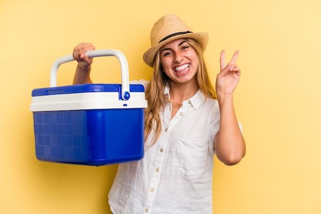 黄色の背景に分離された冷蔵庫を持っている若い白人女性は、指で平和のシンボルを示して楽しくてのんきです。