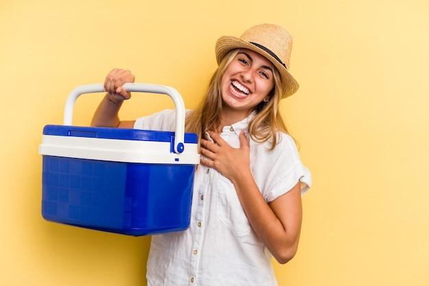 黄色の背景に分離された冷蔵庫を保持している若い白人女性は、胸に手を置いて大声で笑います。