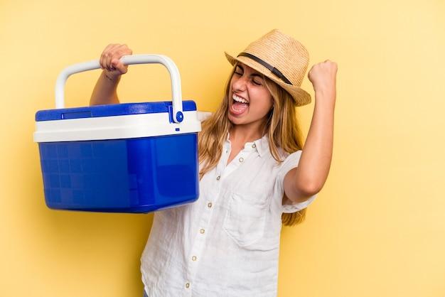 勝利、勝者の概念の後に拳を上げる黄色の背景に分離された冷蔵庫を保持している若い白人女性。