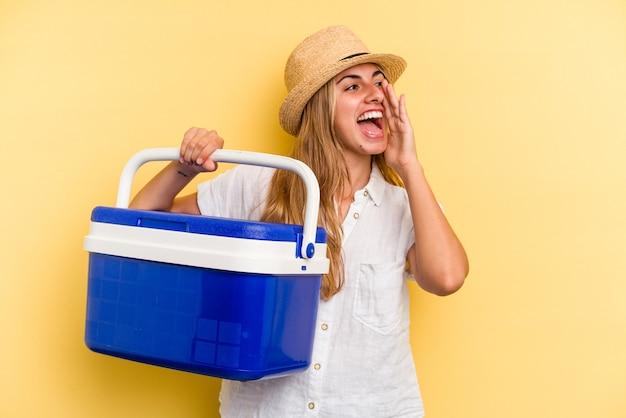 黄色の背景に分離された冷蔵庫を持って叫び、開いた口の近くで手のひらを保持している若い白人女性。