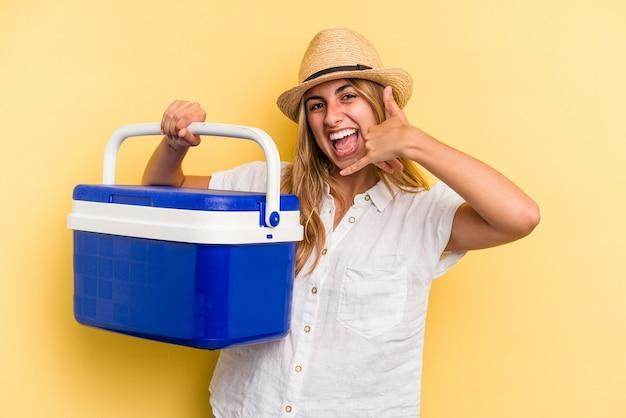 指で携帯電話の呼び出しジェスチャーを示す黄色の背景に分離された冷蔵庫を保持している若い白人女性。