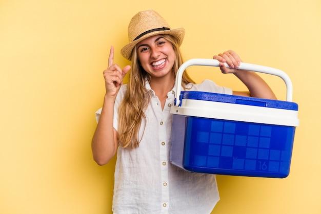 指でナンバーワンを示す黄色の背景に分離された冷蔵庫を保持している若い白人女性。