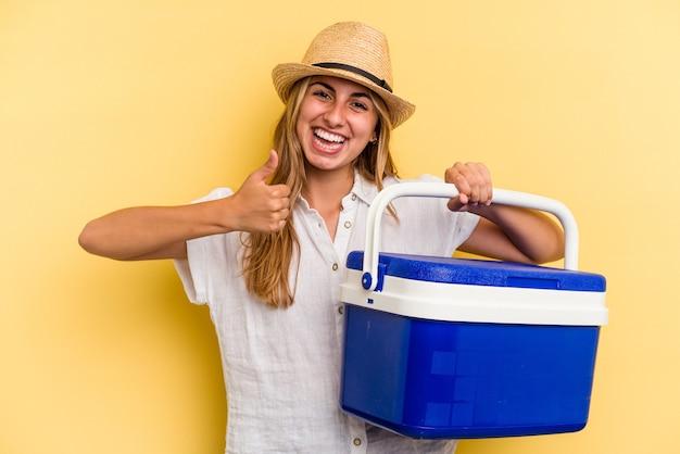 笑顔と親指を上げて黄色の背景に分離された冷蔵庫を保持している若い白人女性