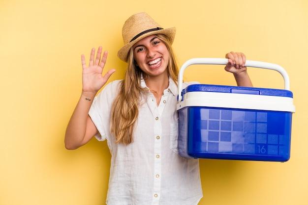 黄色の背景に分離された冷蔵庫を保持している若い白人女性は、指で5番を示して陽気に笑っています。