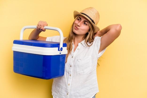 頭の後ろに触れて、考えて、選択をする黄色の背景に分離された冷蔵庫を保持している若い白人女性。
