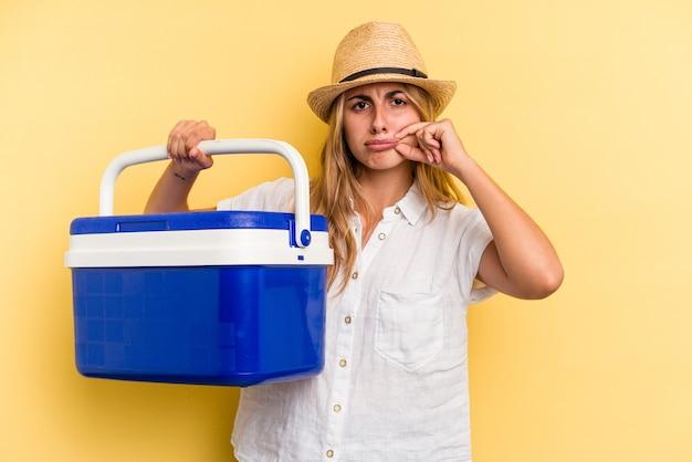 秘密を保持している唇に指で黄色の背景に分離された冷蔵庫を保持している若い白人女性。