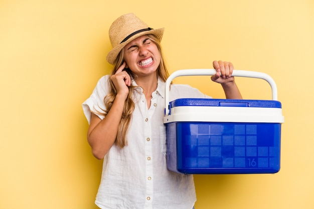 Young caucasian woman holding refrigerator isolated on yellow background  covering ears with hands.