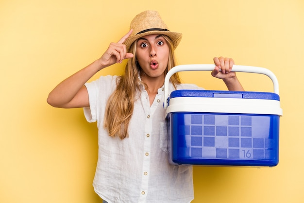 Young caucasian woman holding refrigerator isolated on yellow background  having an idea, inspiration concept.
