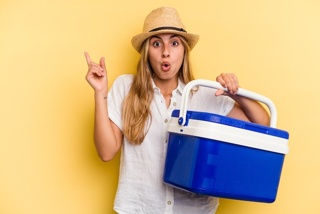 Young caucasian woman holding refrigerator isolated on yellow background  pointing to the side