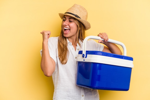 Young caucasian woman holding refrigerator isolated on yellow background  points with thumb finger away, laughing and carefree.