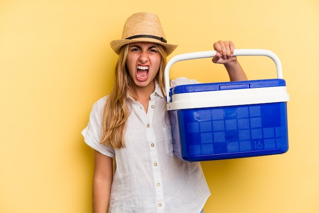 Young caucasian woman holding refrigerator isolated on yellow background  screaming very angry and aggressive.