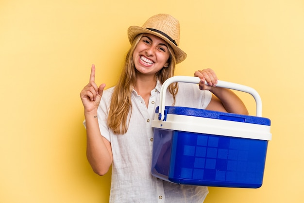 Young caucasian woman holding refrigerator isolated on yellow background  smiling and pointing aside, showing something at blank space.
