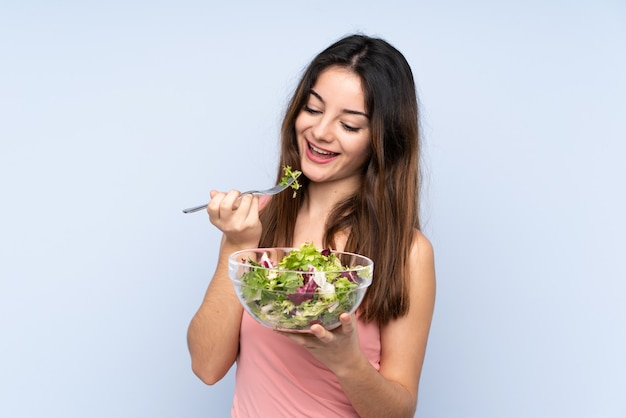 Young caucasian woman holding a salad on blue wall