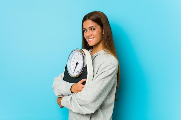 Young caucasian woman holding a scale isolated on a blue wall