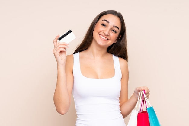 Молодая кавказская женщина, держащая хозяйственные сумки и кредитную карту