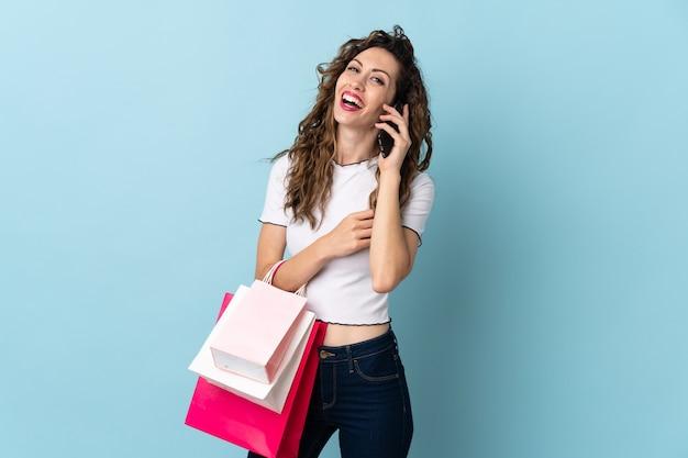 Молодая кавказская женщина держит сумки и звонит другу по мобильному телефону