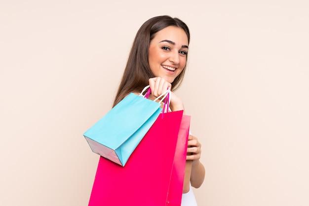 Молодая кавказская женщина, держащая хозяйственные сумки и оглядывающаяся назад