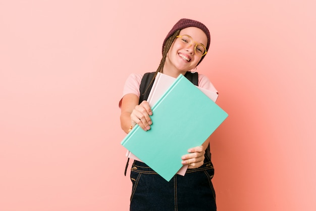 Young caucasian woman holding some notebooks cheerful smiles pointing to front.
